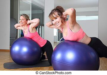 Two women in a fitness center on a Fitness Ball - Two women...