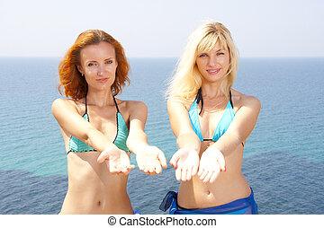 Two women in bikini inviting to sea