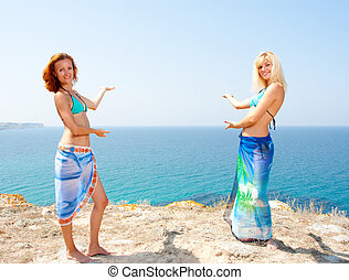 Two women in bikini inviting to sea