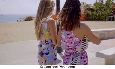 Two women in colorful summer dresses strolling together...