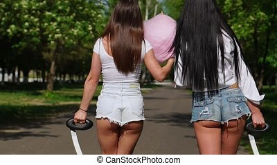 Two women in denim shorts and white t-shirts close - up go...