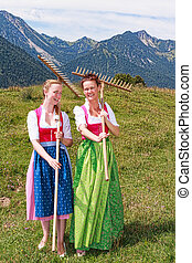 Two women in dirndl with rakes have fun at work
