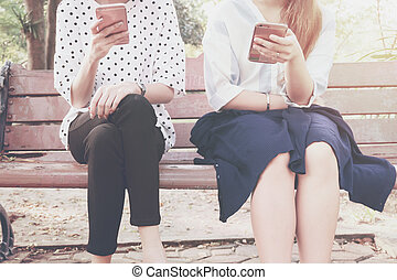 Two women in disinterest moment with smart phones in the outdoor, concept of relationship apathy and using new technology and smartphone addiction. vintage tone