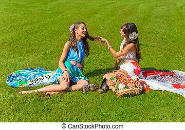 two women in flowers park in summer dresses