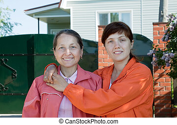 Two  women  in front of  home