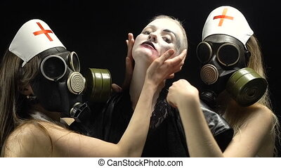 Two women in gas mask with woman in black