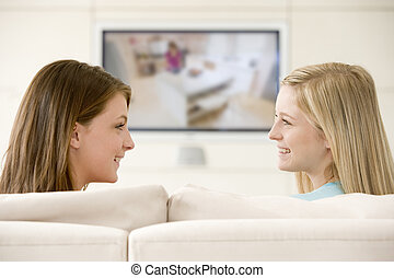 Two women in living room watching television smiling