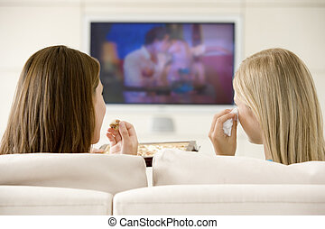 Two women in living room watching television eating chocolates a