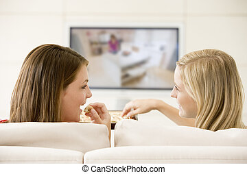 Two women in living room watching television eating...