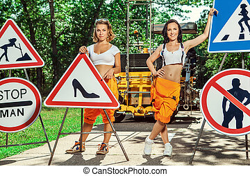"""Two women in orange overalls are mounting """" No Men"""" signs on the road."""