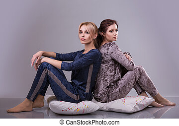 Two women in pajamas sit on pillows on a gray background....