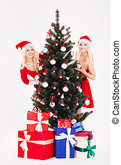 Two women in santa cloth standing near christmas