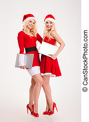 Two women in santa cloth standing with laptop computers