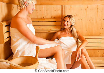 Two women in sauna - Two women enjoying a hot sauna, having...