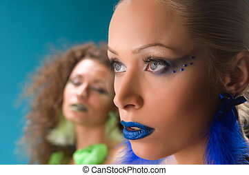 Two women in studio on blue background