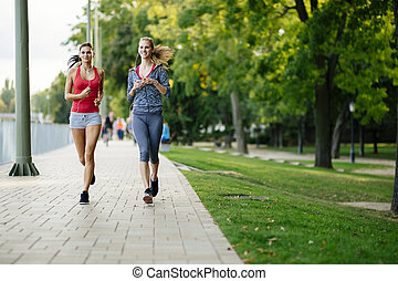 Two women jogging in park