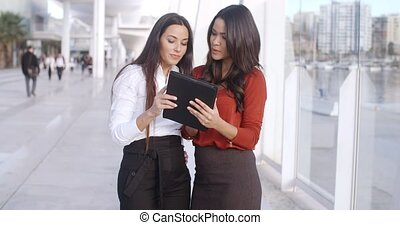 Two women laughing at a tablet computer - Two attractive...