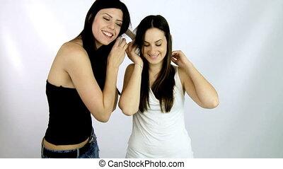 two women listen to music dancing