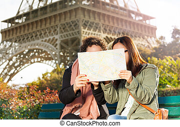 Two women looking at map during excursion in Paris