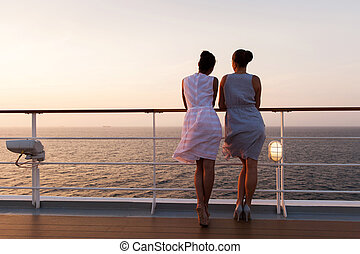 two women looking at sunrise on cruise ship