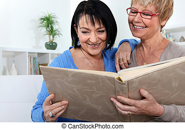 Two women looking through family photo album