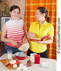 women making Easter cake with cookbook