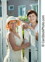 Two women near fence wicket - Two happy women near fence...