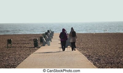 Nordic walking - Two women Nordic walking on a path by the...