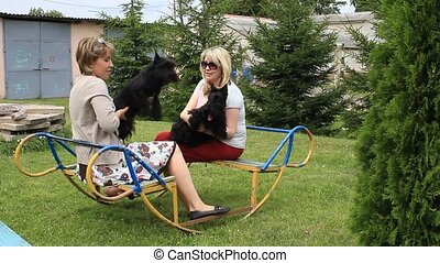 Two women on a swing with a dog in her arms