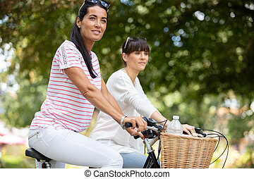 two women on bikes in the park