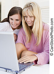 Two women on patio using laptop smiling