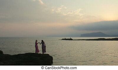 Two women on vacation having fun together at the seashore on a summer evening