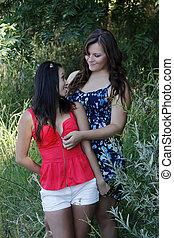 Two Women Outdoors Unzipping Top Caucasian Asian