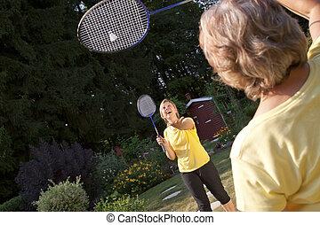 Two women playing badminton