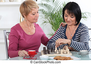 Two women playing chess and having a chat