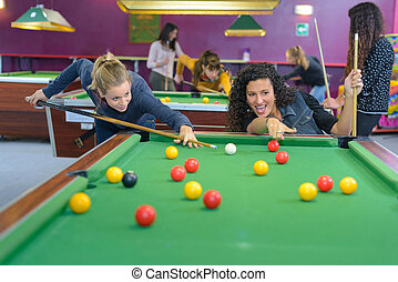 Two women playing pool