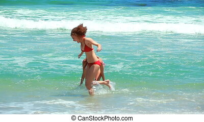 Two women playing together in the sea