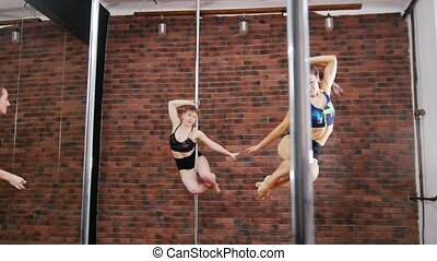 Two women practicing a pose in a pole fitness class. Dynamic...