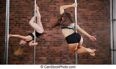 Two women practicing in a pole fitness class on the...