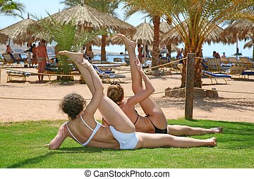 Two women practise on a beach