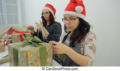 Two women prepare new year presents for Christmas holidays inside