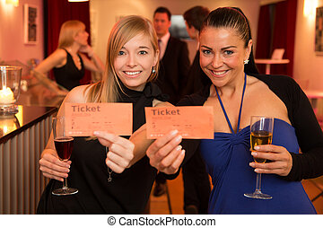 Two women presenting theatre or movie tickets - Two...