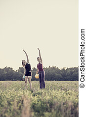 Two women reaching for the sky with copy space