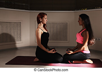 Two women relaxing in dark yoga class