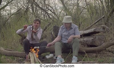 Two women roasting marshmallows on a fire - Elderly and...