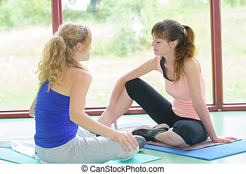 Two women sat talking on yoga mats