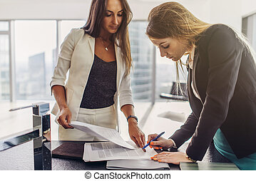 Two women signing a contract standing in modern appartment