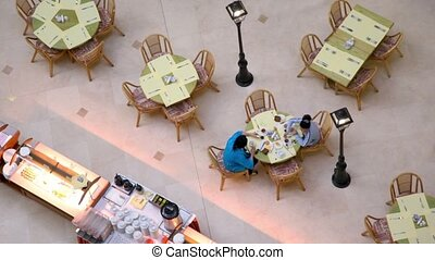 Two women sit at table near buffet in cafe, view from above