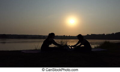 Two Women Sit on Mats And Keep Their Legs Stretched at Sunset in Slo-Mo