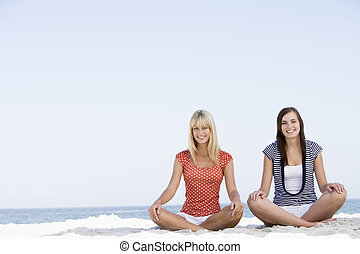 Two women sitting and meditating on a beach